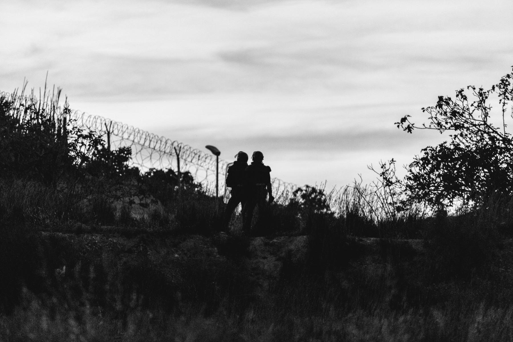 Dos agentes de policía frente a la frontera que separa Melilla y Marruecos (ÁNGELA RÍOS / EUROPA PRESS). (1)