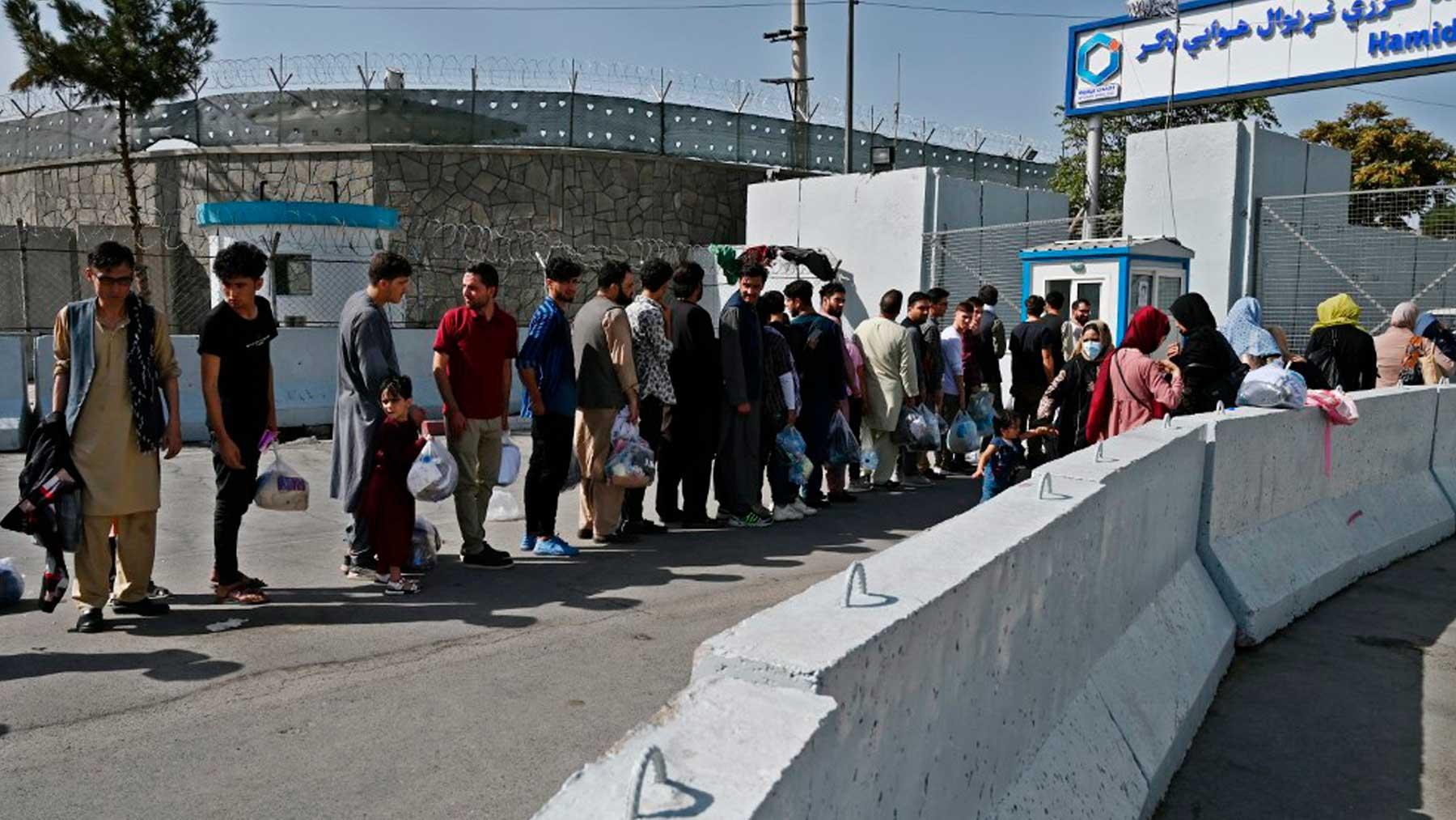 Una cola de ciudadanos afganos en la puerta principal del aeropuerto de Kabul esperan para entrar y ser evacuados. Foto: AFP