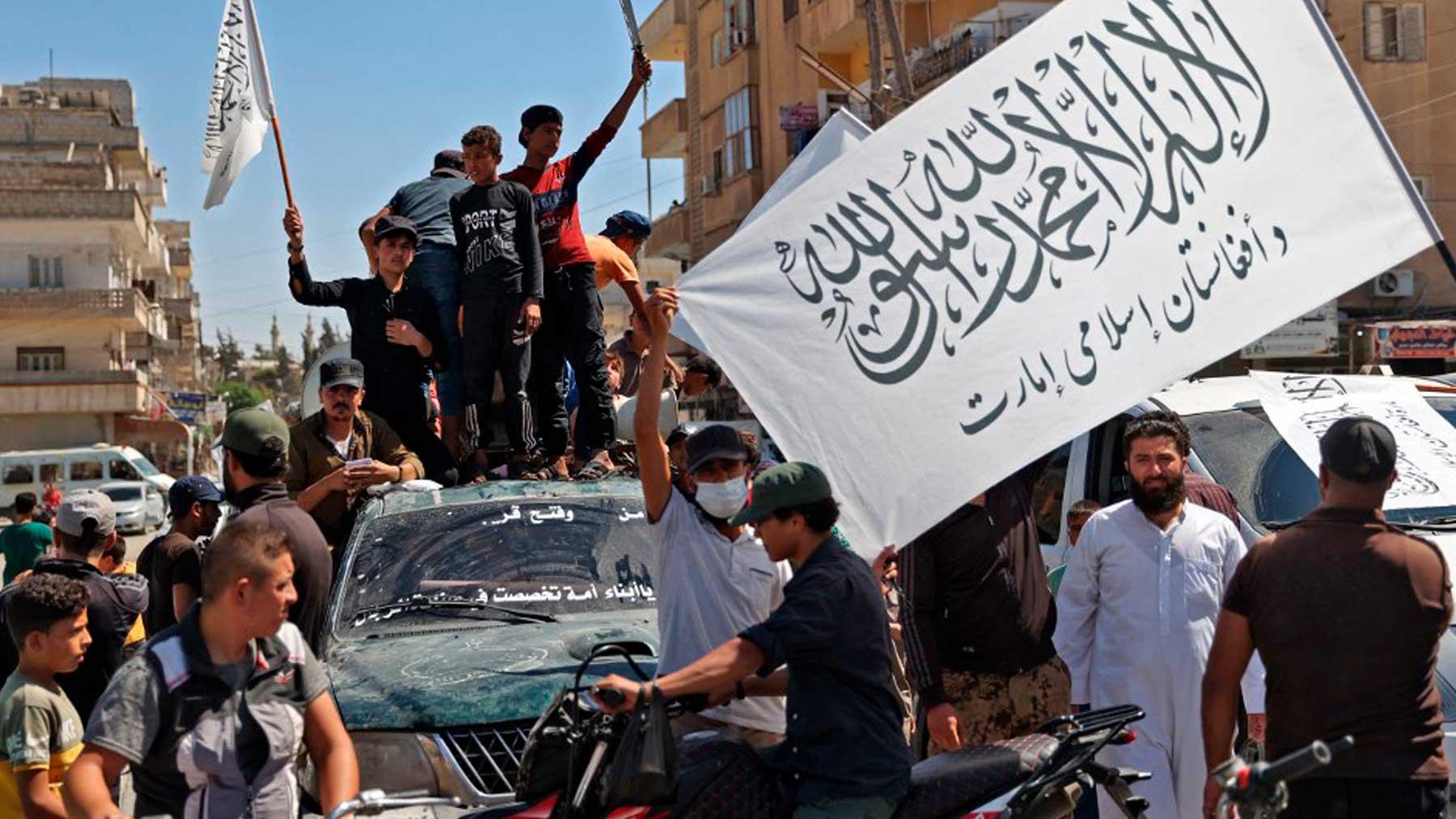 Ciudadanos sirios celebran la victoria de los talibanes ondeando su bandera. Foto: AFP