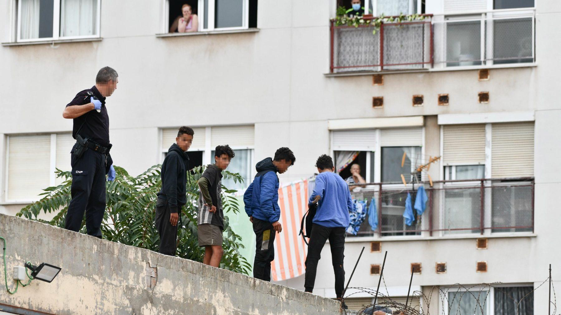 Un agente trabaja para que un grupo de menas abandone el tejado de una nave industrial en Ceuta (EUROPA PRESS).
