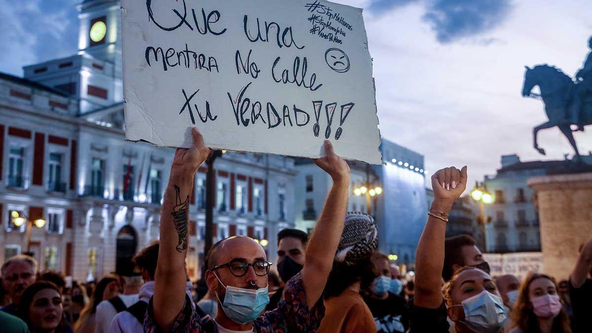 Un manifestante sostiene una pancarta durante una concentración en la Puerta del Sol