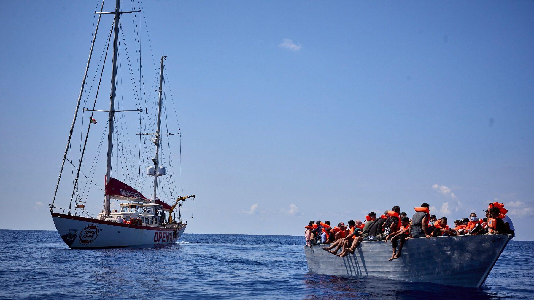 Un barco de Open Arms, junto a una patera (JESÚS HELLÍN / EUROPA PRESS).