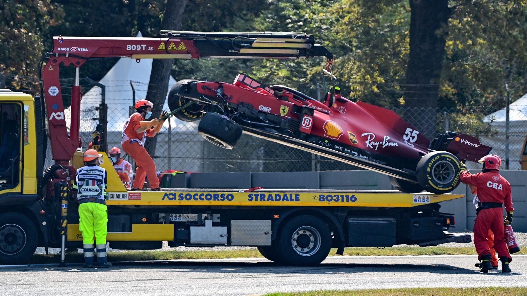 Los operarios retiran el Ferrari de Carlos Sainz tras su accidente en Monza. (AFP)