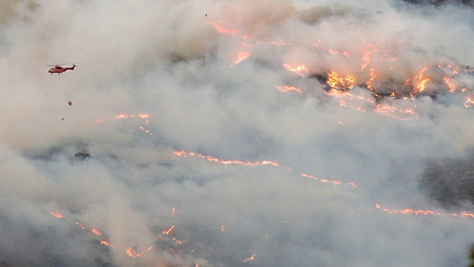 Un helicóptero sobrevuela el fuego desatado en Sierra Bermeja (ÁLEX ZEA / EUROPA PRESS). (1)