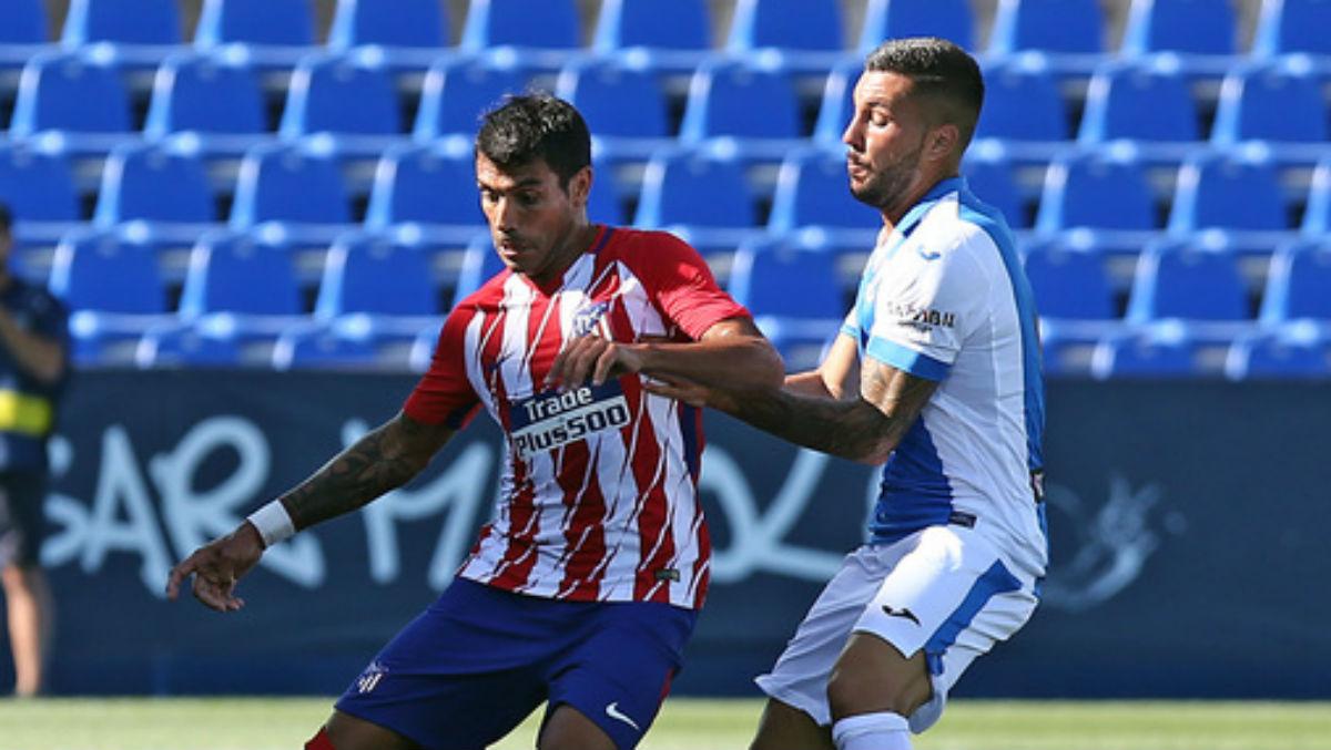 Augusto Fernández protege el balón ante Guerrero. (clubatleticodemadrid.com)