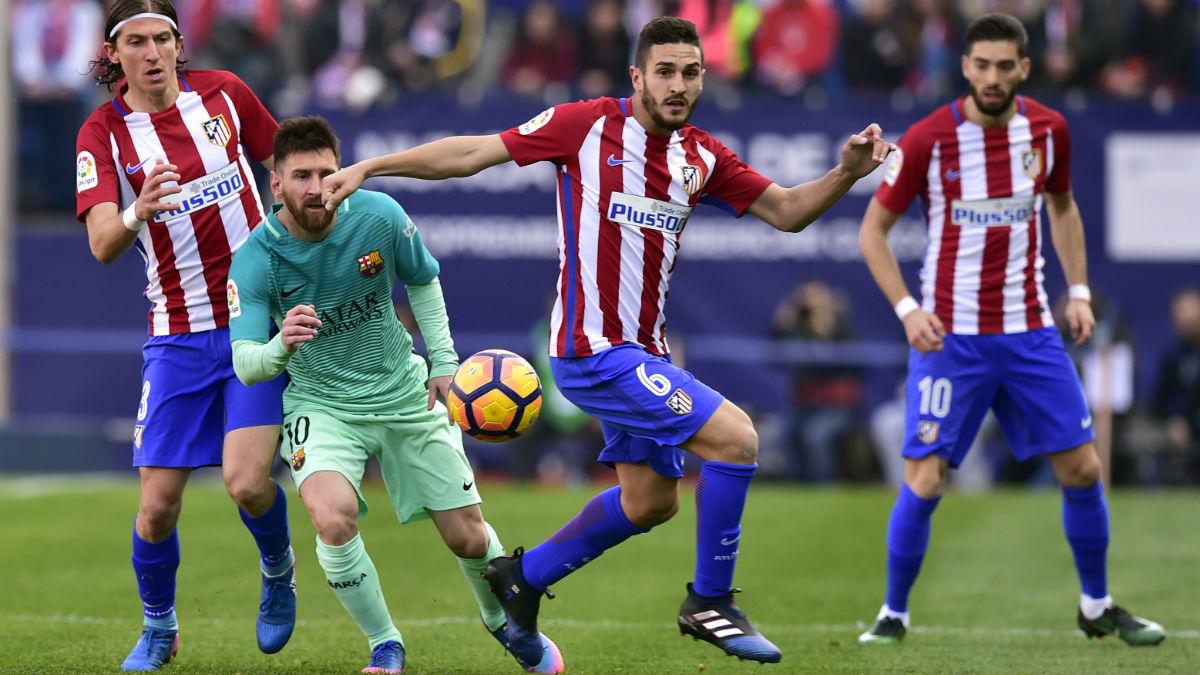 Carrasco y Messi disputan un balón durante el Atlético vs Barcelona de la temporada pasada. (AFP)
