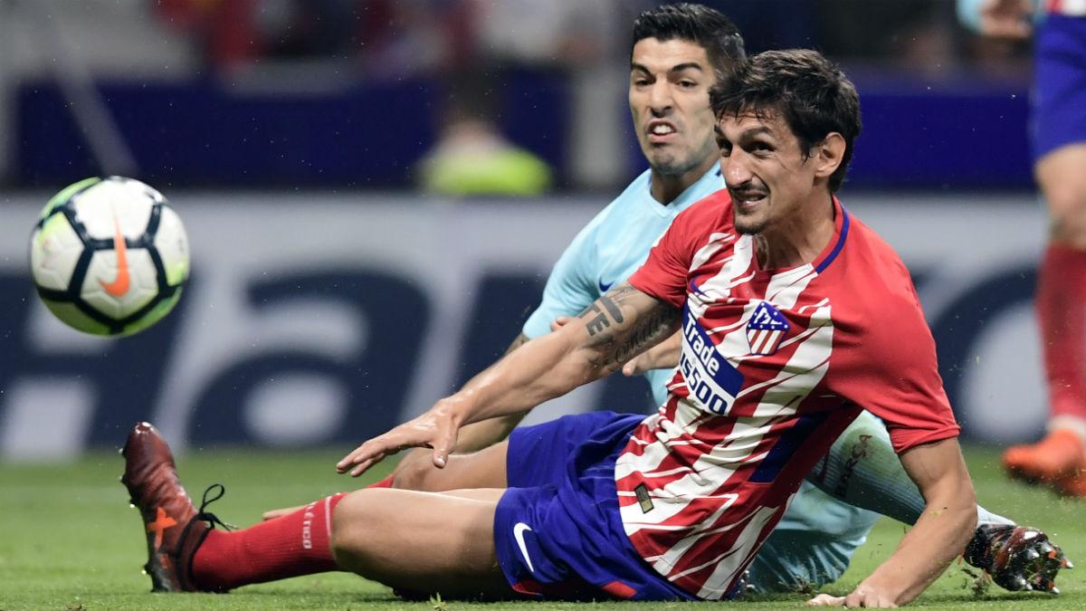 Savic disputa un balón con Luis Suárez. (AFP)