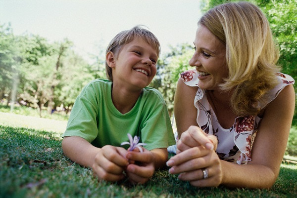 Tilted portrait of a mother and son relaxing in the grass