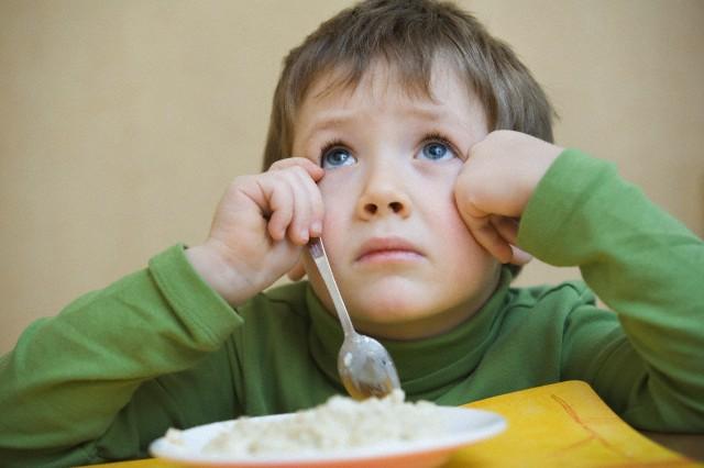 Portrait young boy gazing upwards while eating