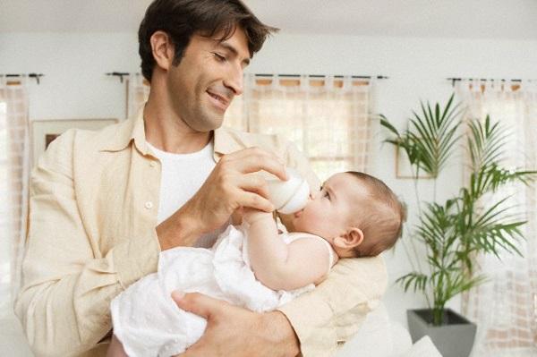 Father feeding infant --- Image by © Maria Teijeiro/cultura/Corbis