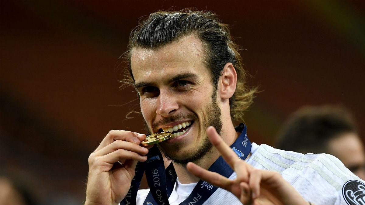 Bale muerde la medalla de la Undécima. (Getty)