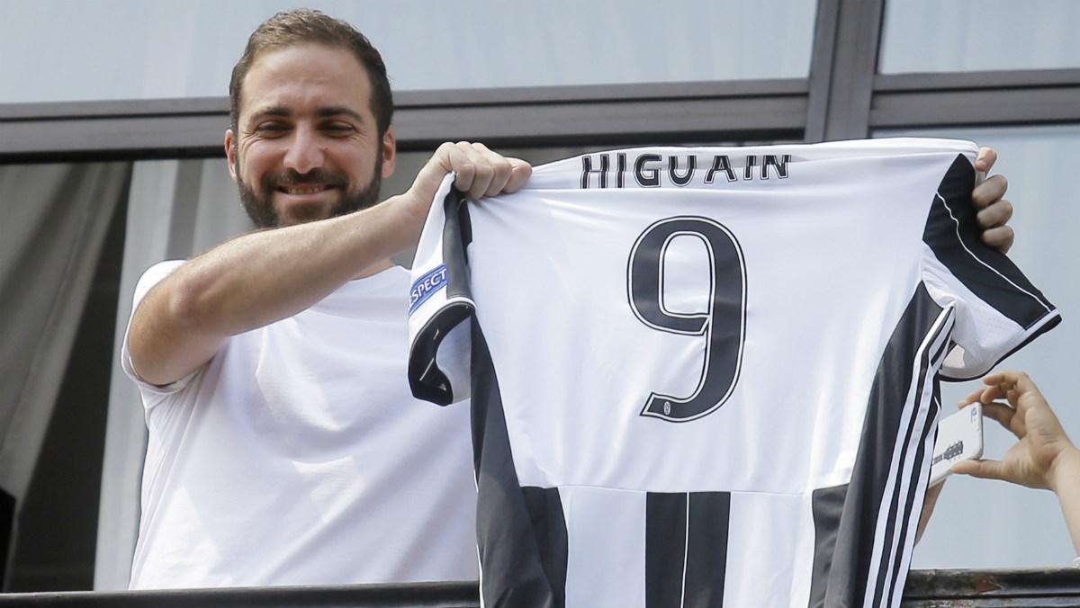 Higuaín enseña a los aficionados la camiseta de la Juve. (AFP)