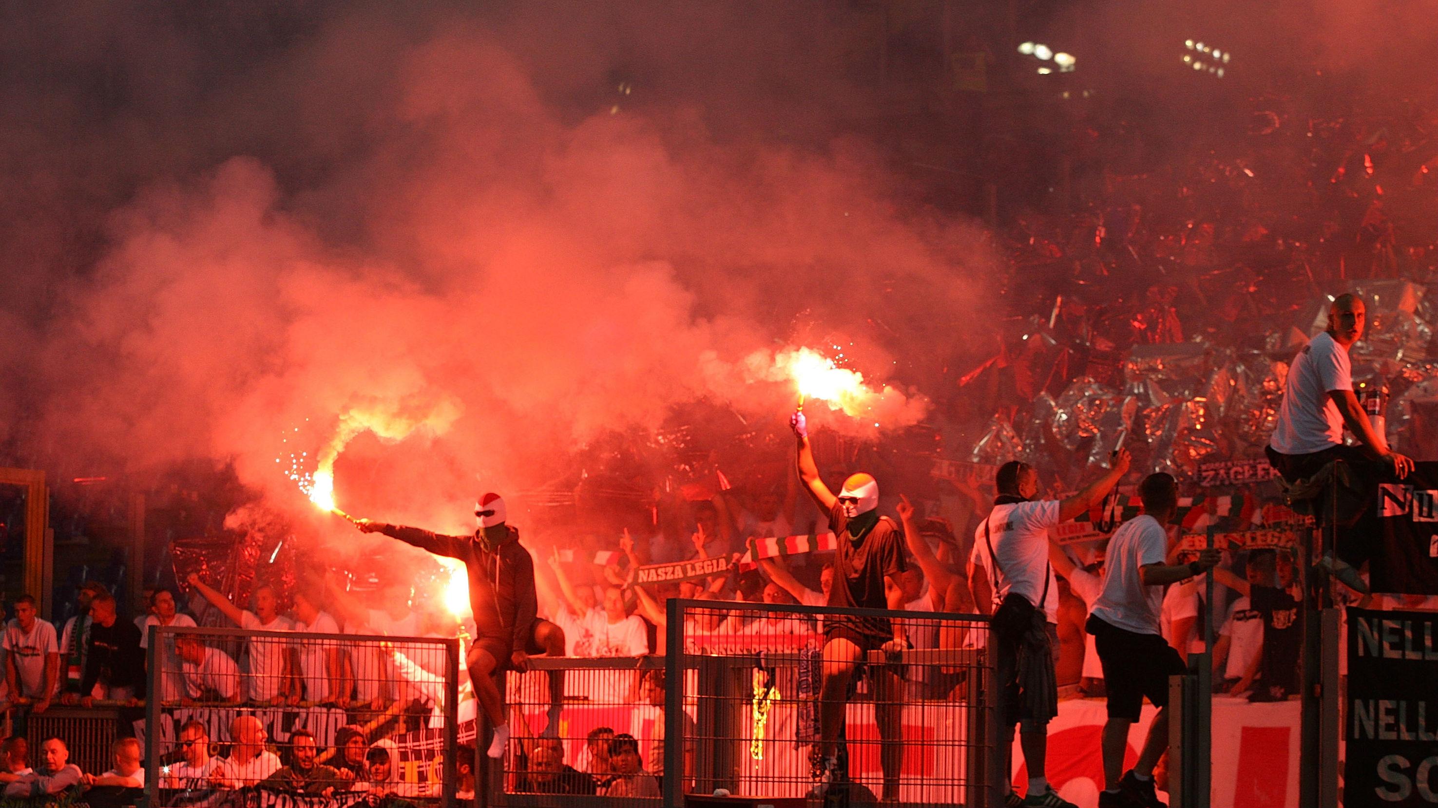 Aficionados del Legia de Varsovia encienden bengalas. (Getty)