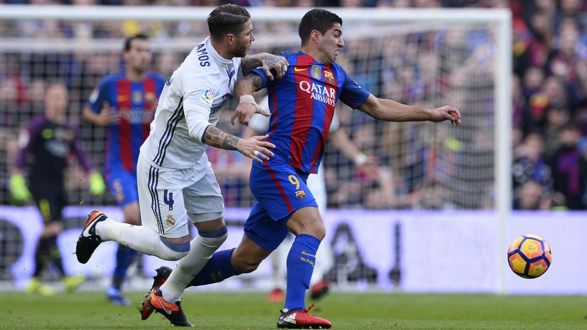 Luis Suárez pugna con Sergio Ramos en el Clásico. (AFP)