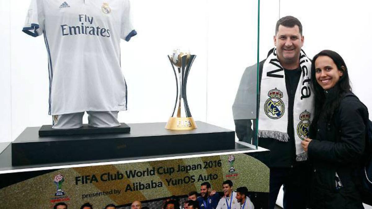 Aficionados del Real Madrid posan junto a la Copa Mundial de Clubes. (realmadrid.com)