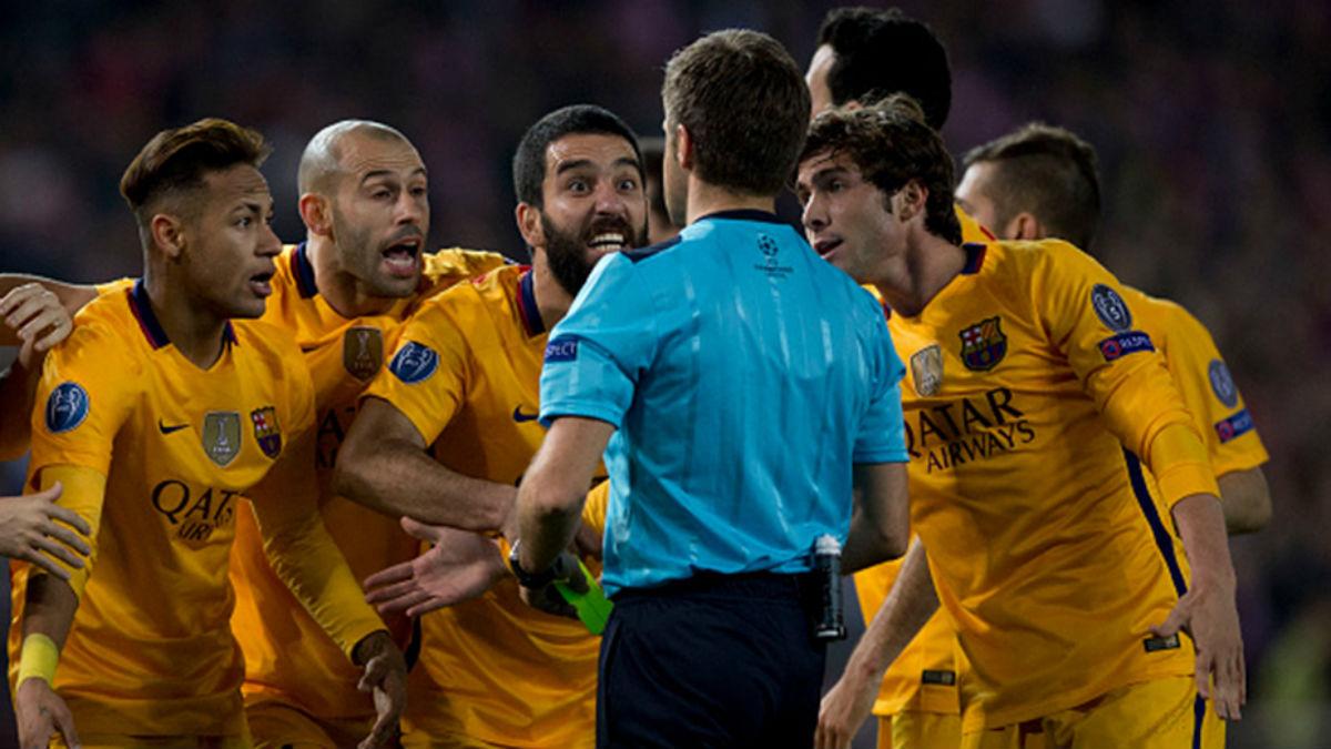 Los jugadores del Barça rodean a un árbitro para protestar una acción en la Champions. (AFP)