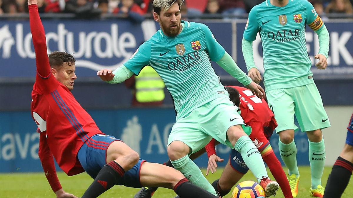 Oriol Riera entra a Messi en un partido de esta temporada. (AFP)