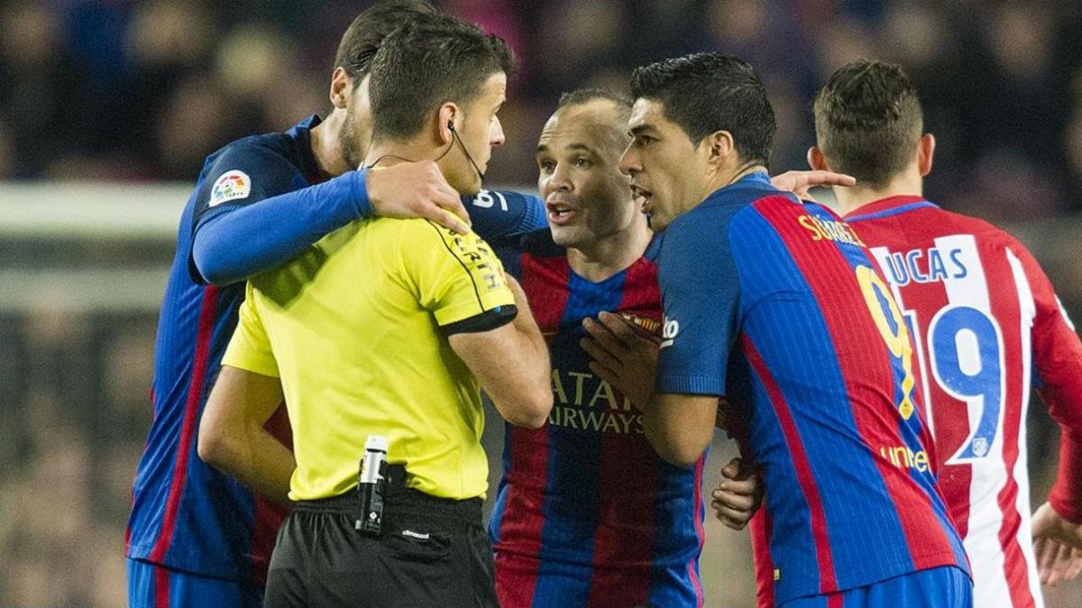 Los jugadores del Barcelona rodean a un árbitro durante un duelo con el Atlético. (AFP)