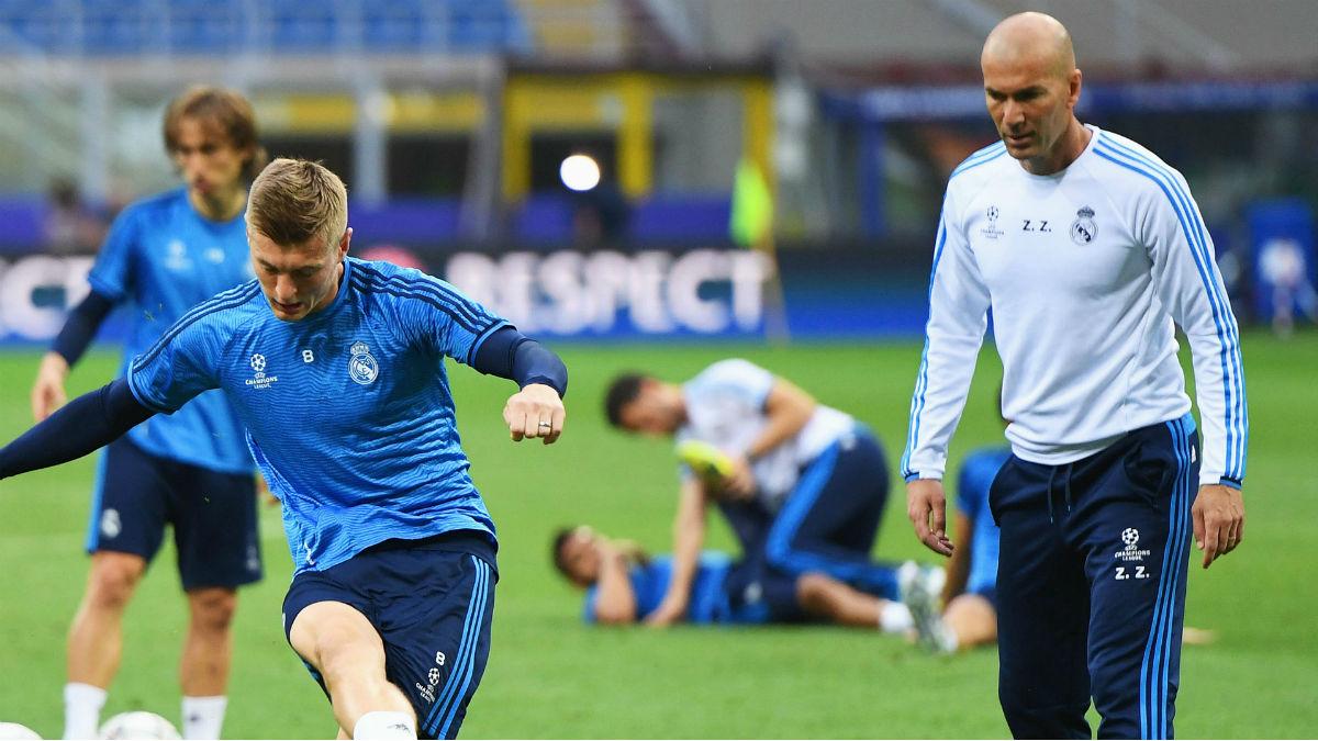 Kroos golpea el balón ante la atenta mirada de Zidane.