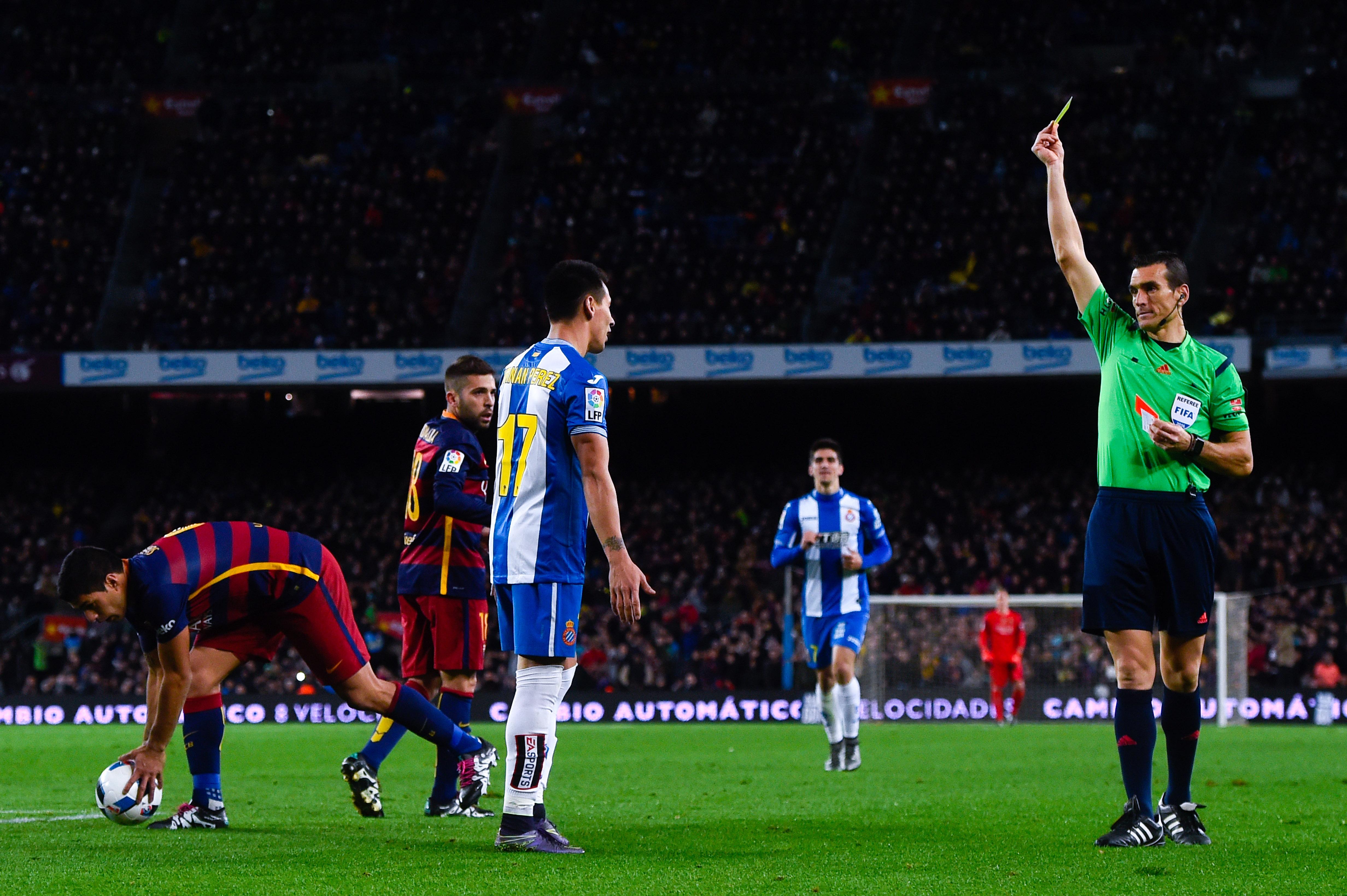 Una imagen habitual de los derbis: un jugador del Espanyol recibiendo una amarilla contra el Barcelona. (Getty)