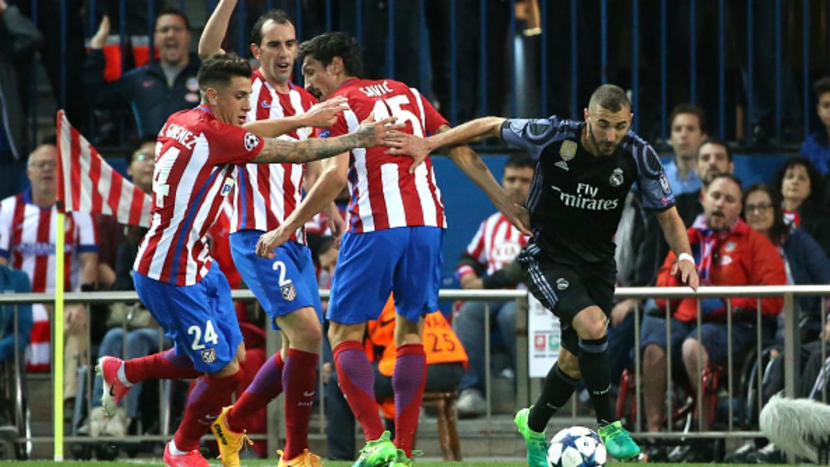 Benzema se marcha de los tres defensores del Atlético (Getty).