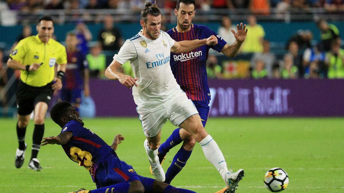 Bale disputa un balón con Umtiti y Busquets. (Getty)