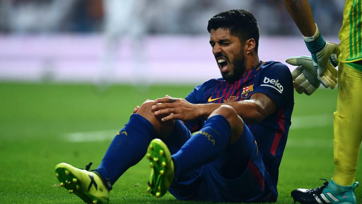 Luis Suárez se duele tras dañarse la rodilla. (Getty)