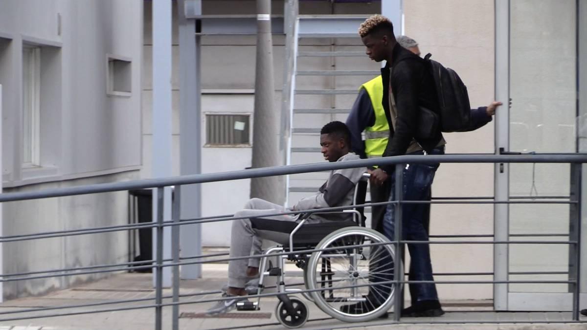Umtiti lleva en silla de rueda a Dembélé.