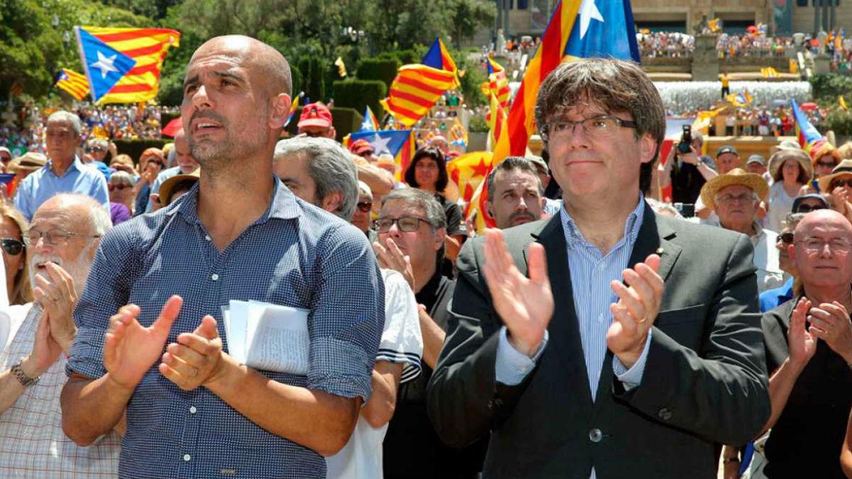 Pep Guardiola aplaude junto a su padrino Puigdemont.
