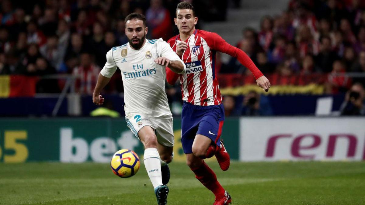 Dani Carvajal, durante el derbi madrileño, conduce el balón perseguido por Lucas Hernández (Getty).