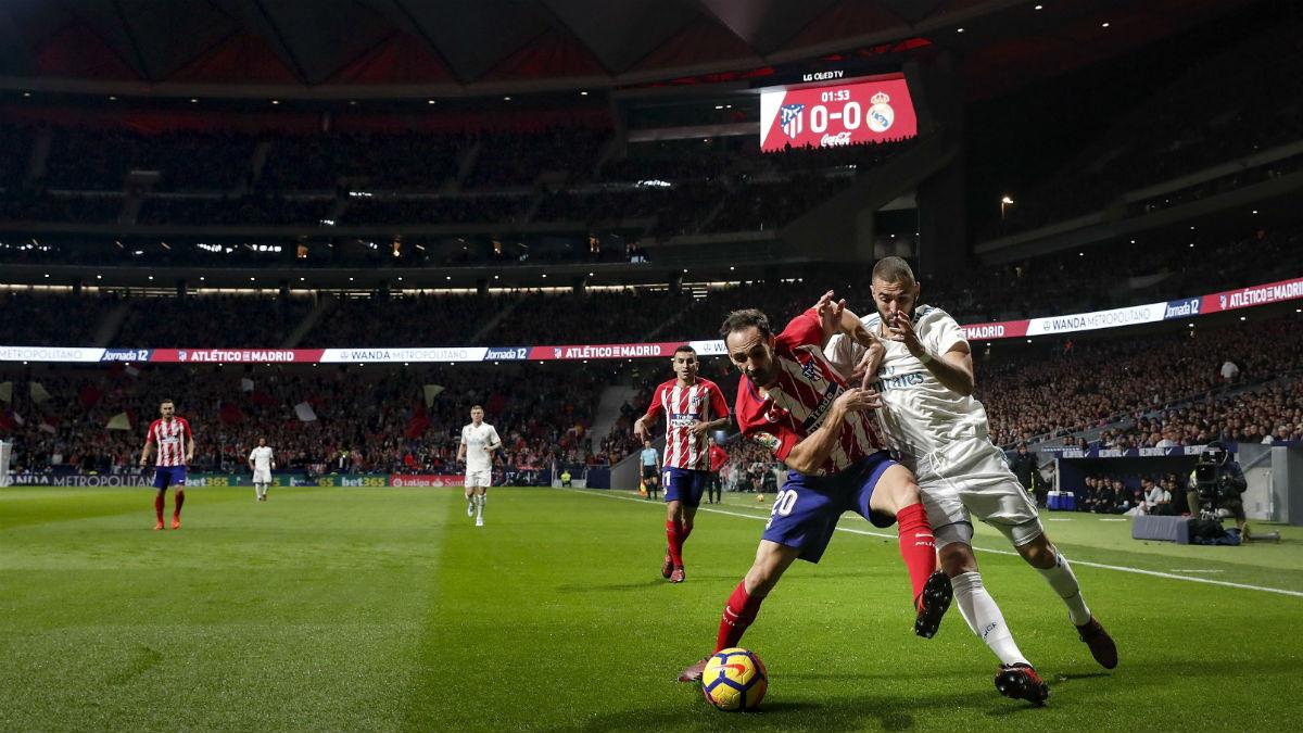 Juanfran y Benzema pelean un balón. (Getty)