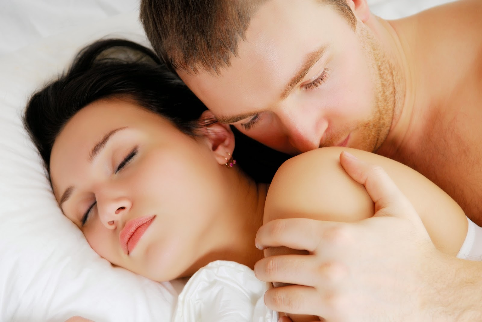 Beautiful married people lying in bed and stroking...