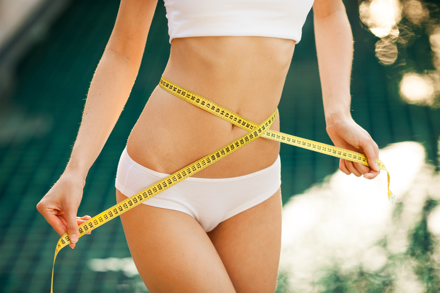 Woman measuring her waistline. Perfect Slim Body. Outdoor