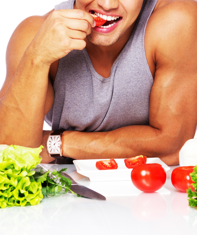 Handsome man biting tomato in studio