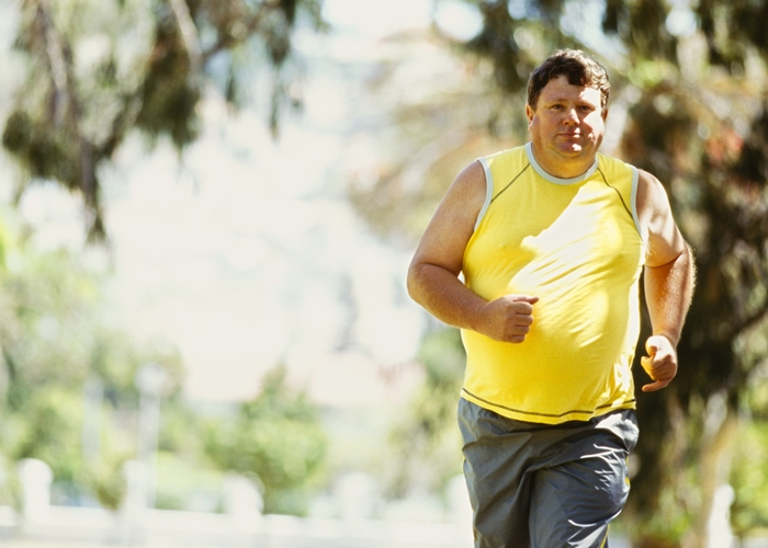 portrait of a mid adult man jogging in a park
