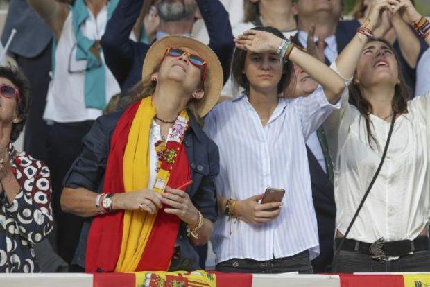 La infanta Elena acudía al desfile con sombrero y una bandera de España al cuello, acompañada de su hija Victoria Federica / Gtres