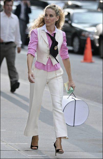 Carrie Bradshaw con unos pantalones blancos conjuntados con una blusa rosa de rayas blancas y un chaleco haciendo juego./Gtres